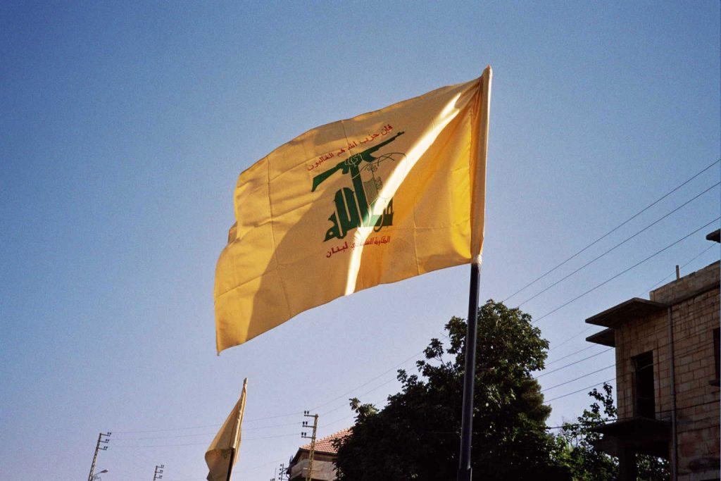 Hizbollah on ollut mukana Libanonin hallituksessa vuodesta 2005 lähtien ja se on tukenut  Bašar al-Assadin hallintoa Syyriassa. Hizbollahin lipussa on kuvattuna Kalashnikov-konepistooli.